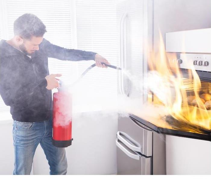 Man extinguishing a kitchen fire on his stove